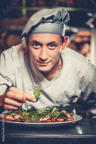 Wall mural Food concept. Preparing traditional italian pizza. Young handsome chef in white uniform and gray hat decorate ready dish with green rucola herbs in interior of modern restaurant kitchen. Ready to eat.