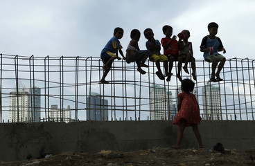 Children sit on iron bars at a construction site in Jakarta