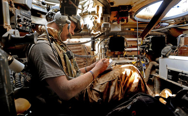 Britain's Prince Harry sits in his Spartan armoured vehicle as he communicates with other units by radio in Helmand province