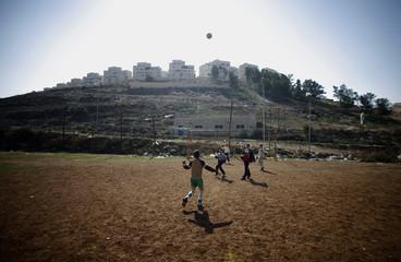 Palestinian children play soccer outside the settlement of Har Homa