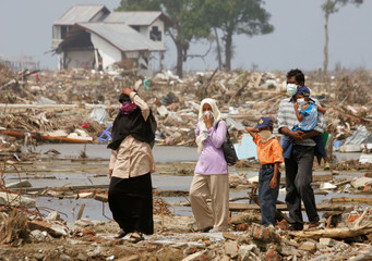 Acehnese residents roam amid the debris of houses damaged by the tsunami in Banda Aceh.