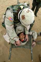 A U.S. Army medic checks another soldier on a stretcher during an exercise December 8, 2002 in the n..