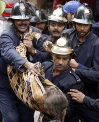 Firemen carry out body of a victim from the debris of a building that collapsed in Mumbai