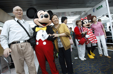 Chinese tourists pose for a picture with Mickey and Minnie Mouse on a cruise boat in Washington