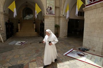 A Catholic nun walks past posters welcoming Pope Benedict XVI outside the Latin Patriarchate in Jerusalem