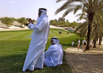 Spectators dressed in traditional Arabic attire watch the Dubai Desert Classic.
