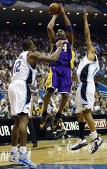 Los Angeles Lakers guard Kobe Bryant shoots between Orlando Magic center Dwight Howard and Courtney Lee in Orlando