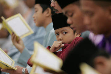Young Bruneian gestures as he sits during prayer at a mosque in Bandar Seri Begawan