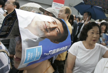 Voter uses pamphlet of Japan's ruling LDP in pamphlets to avoid getting wet during campaign rally in Tokyo