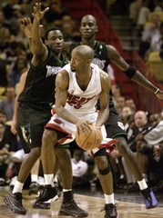 MIAMIS CARTER GUARDED BY MINNESOTAS GARNETT AND BILLUPS.