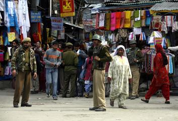 Kashmiri people walk past Indian policemen during cordon and search operation in Srinagar