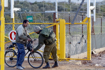 ISRAELI SOLDIER CHECKS THE BAG OF A PALESTINIAN MAN AT THE SECURITY FENCE AT THE ENTRANCE TO QALQILYA.