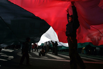 Children carry a Palestine flag during a protest  in Rabat