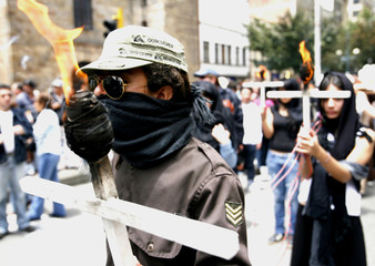 Demonstrators hold burning crosses during a march in Bogota