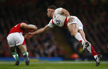 Wales' Leigh Halfpenny evades a tackle from England's Joe Worsley during their Six Nations rugby union match in Cardiff