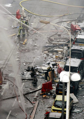 French firemen and rescue crews work at the debris-scattered scene of a gas explosion in central Lyon which injured 17 people