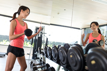 Sport Woman lifting up dumbbell and taking selfie with mobile phone in gym room