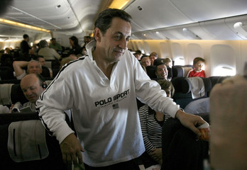 France's UMP political party presidential candidate Nicolas Sarkozy speaks with passengers in a plane, while on his way to the French West Indies