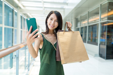 Young woman holding shopping bag and take selfie by mobile phone
