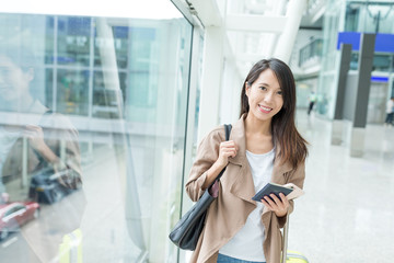 Woman holding passport and cellphone in airport