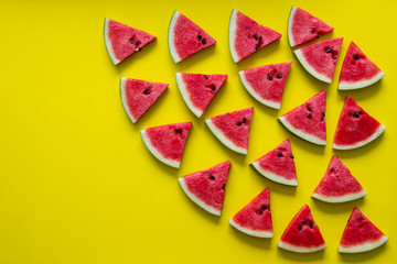 Pieces of red watermelon on yellow background.