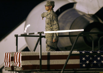 Airman lowers the lift with the transfer cases containing bodies of Army personnel at Dover Air Force Base