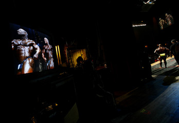 Professional bodybuilders are seen on a television screen backstage during the Prejudging of the Arnold Classic at the 2008 Arnold Schwarzenegger Sports Festival in Columbus