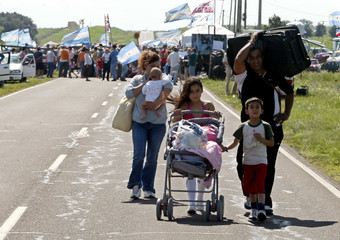 Family carrying their belongings walk along the road linking the Argentine city of Gualeguaychu and the Uruguayan city of Fray Bentos