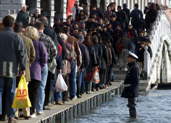 Policemen control people on wooden walkways next near St. Mark's square flooded by high water in Ven..
