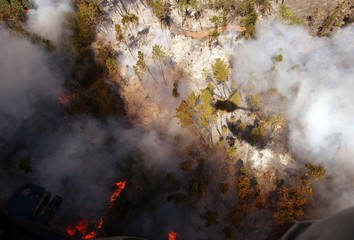 German Puma Helicopter is silhouetted as it dumps water during forest fire in Miranda Do Corvo ...