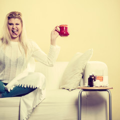 Happy woman showing cup of tea