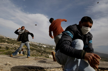 Palestinian youths throw stones at Israeli troops during a protest in Bilin