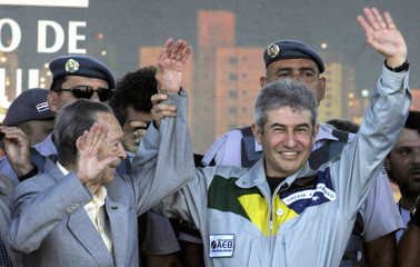 Brazil's astronaut Pontes and his father wave to the crowd during his arrival in Bauru
