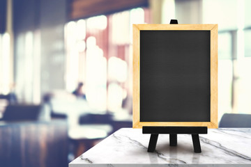 Blackboard with easel on white marble table at blurred people in coffee shop background,Mock up for display or montage of design for online shopping promotion.