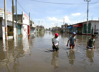 MEXICANS WALK DOWN FLOODED STREET.