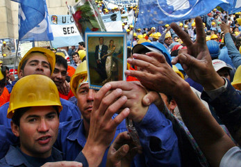 Workers show a picture of late president of Argentina Peron as his body is transferred to a mausuleum in Buenos Aires