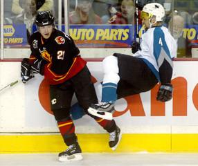 Flames' Ference sends Sharks' McLaren flying through the air on a stiff body check during their NHL game in Calgary