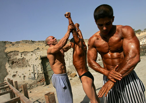 Body builders apply tanning lotion as they prepare for a competition for the title of Mr Afghanistan in Kabul