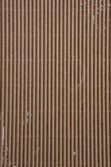 Abstract background of beige corrugated cardboard texture, flat lay. Rough brown backdrop with free space for text.