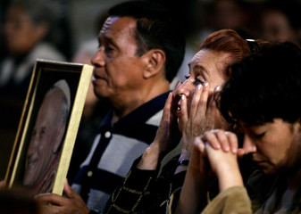 A Mexican worshiper wipes away tears during a mass for the Pope.
