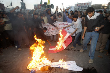 Shi'ite Muslims burn Danish, U.S. and Israeli flags during a religious procession in Karachi