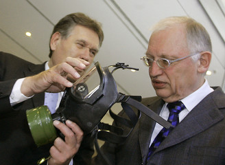 German Economy and Technology Minister Glos displays European Union commissioner for enterprise and industry  Verheugen a gas mask during the conference 'Innovation and Market Viability through Standardization' in Berlin March 27