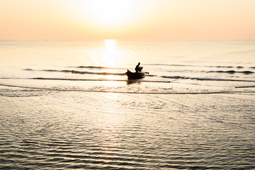 Silhouette of fishing boat and Beautiful tropical sunrise on the beach.