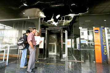 People stand in front of a bank that was attacked with homemade bombs in Sao Paulo