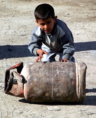Iraqi boy pushes LPG tank used for cooking for refill from petrol station in Baghdad's Sadr city