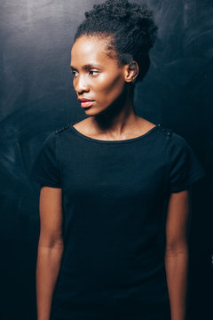 Pretty and young afroamerican woman wearing black t-shirt on dark background. Look at side, serious beautiful face.