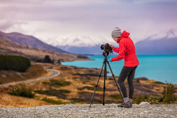 Photographer taking New Zealand travel nature photography. Woman photographer with slr camera on tripod at sunset with beautiful landscape in background. Peter's lookout, famous tourist destination.