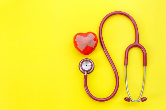 Red stethoscope and red heart shape on yellow background. For check heart or health check up concept