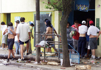 ARGENTINE LOOTERS CARRY GOODS FROM A SUPERMARKET.