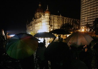Journalists hold umbrellas in the rain as they watch a gun battle in Taj Mahal Hotel in Mumbai